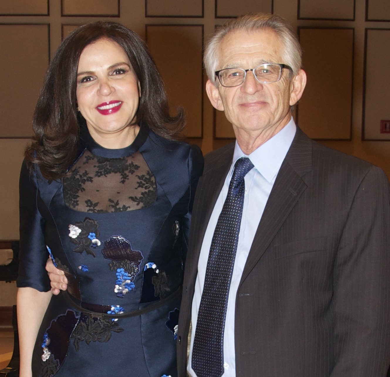 Smiling woman with long dark hair next to smile man with gray hair and glasses