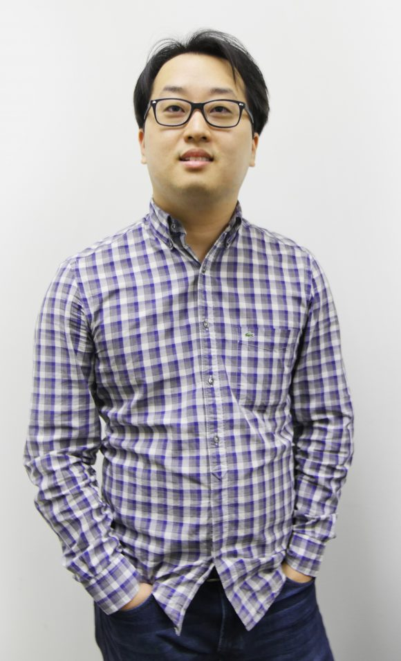 Asian man with dark short hair and glasses, wearing a blue gingham check long sleeve shirt and dark pants.