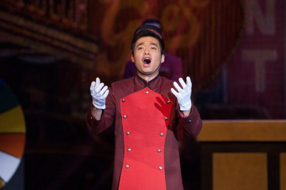 Man in a bellboy suit singing.