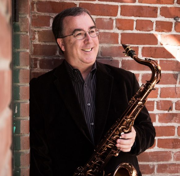 Smiling man in suit and glasses holding a saxophone.