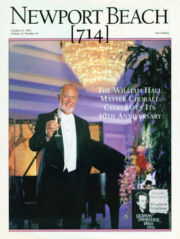 Cover of Newport Beach magazine featuring William Hall dressed in a tuxedo holding a glass of champagne under a crystal chandelier with a piano in the background.