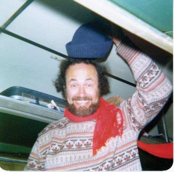 Smiling William hall with raised knit hat, sweater, and scarf while standing in a tour bus.