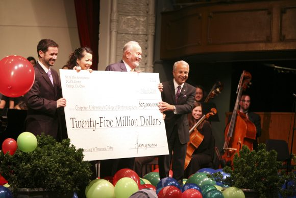 Four people on a stage holding a large replica check for $25M from an anonymous donor with balloons in the foreground and musicians in the background.
