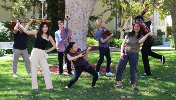 String students taking playful poses with their instruments.