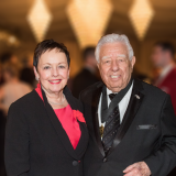 Smiling older woman with short black hair in a black suit with red blouse; smiling older man with white hair in black tuxedo
