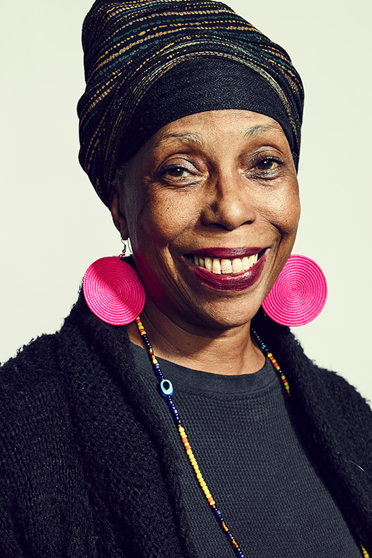 Smiling Black woman with traditional headdress, large pink disc earrings, and black cardigan.