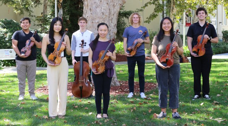 Seven string students lined up on a lawn holding their instruments.