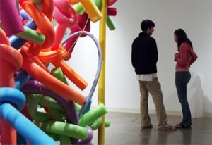 Two people in art gallery with sculpture.