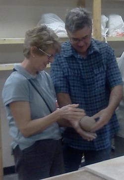 Man and woman holding ceramics.