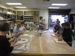 Group of people at table working on ceramics.