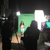Woman being filmed in front of green screen.
