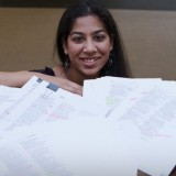 Woman posing with many marked up pages of writing.