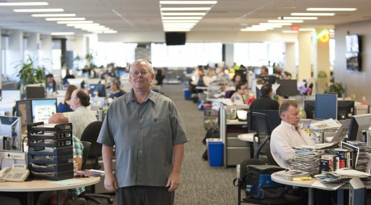 Man standing in office as people work.