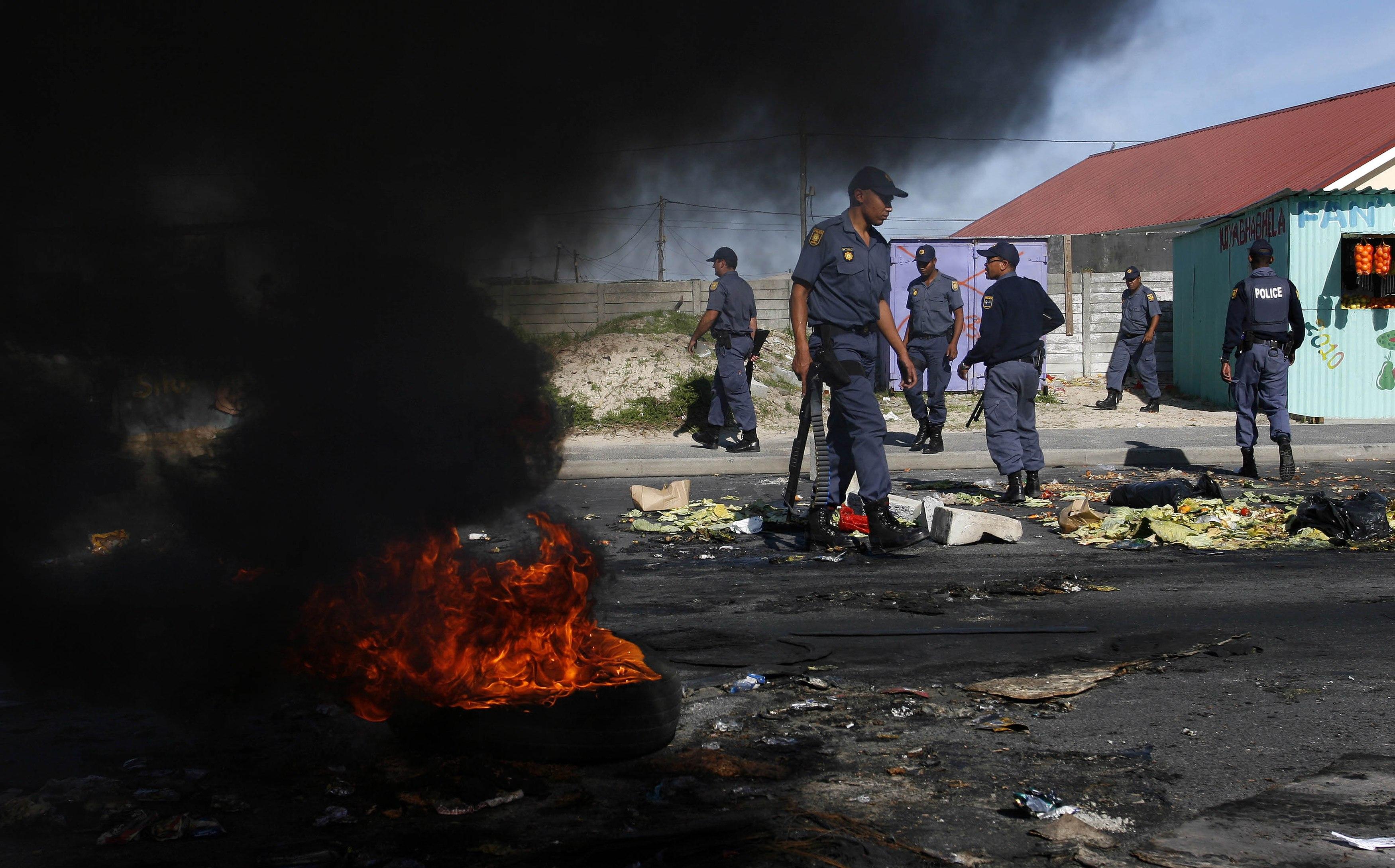 Police behind burning barricades.