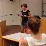Woman reading from paper for presentation.