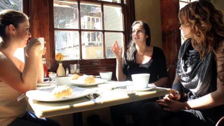 Three women talking in cafe.