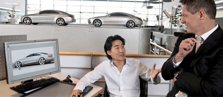 Two men talking at computer with car design.