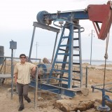 Man standing next to oil well.