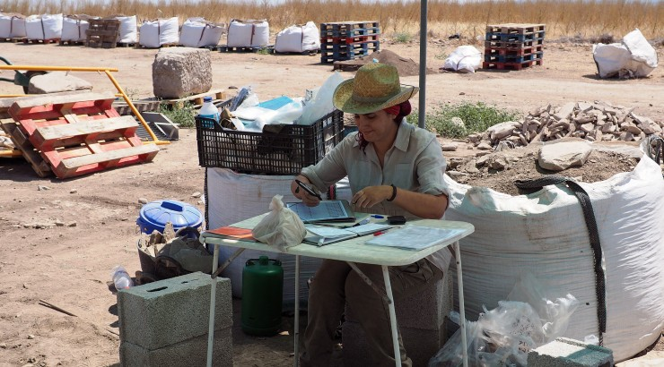 Woman filling out paperwork at outdoor desk.