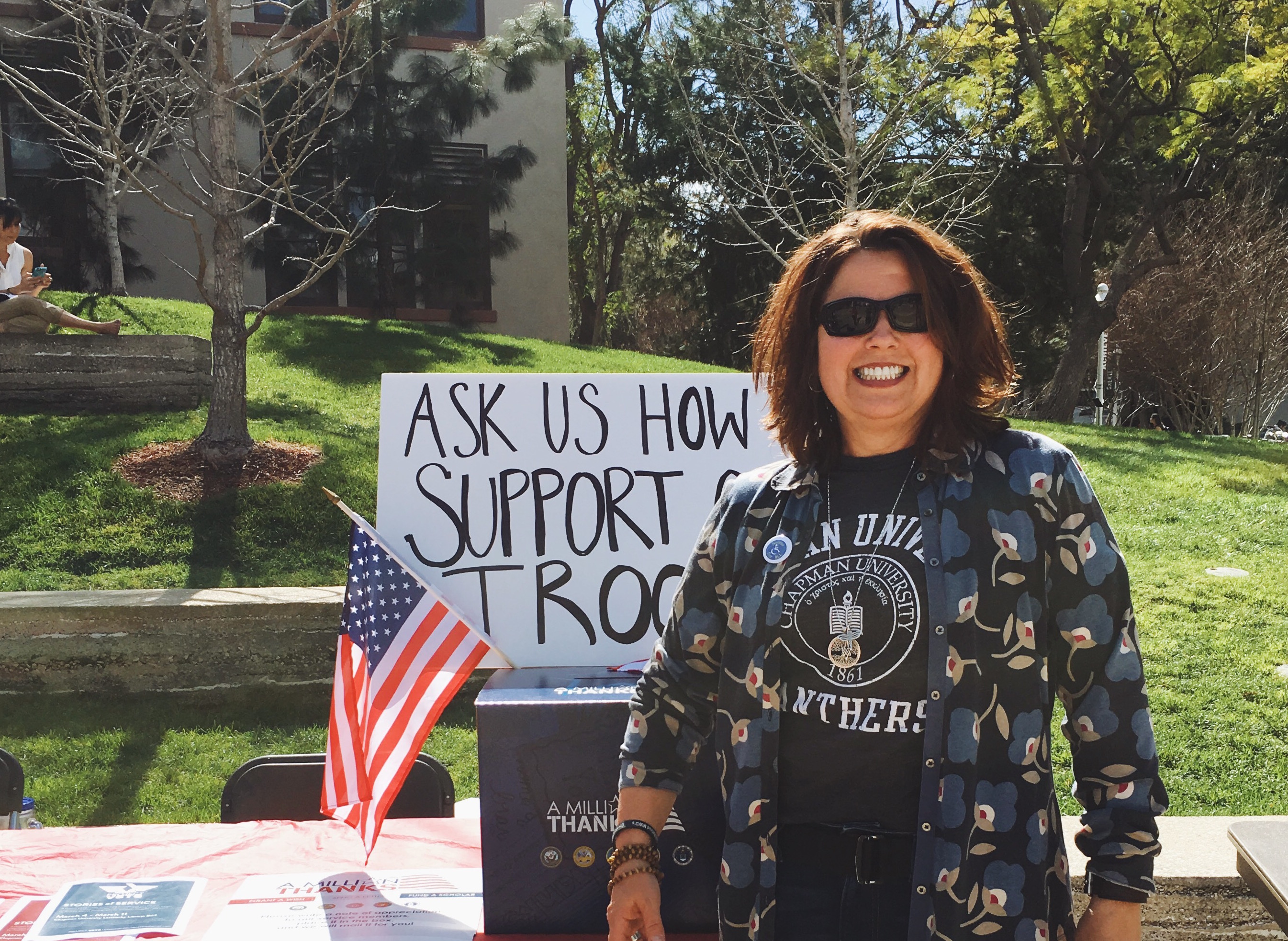 Woman smiling next to fundraising table for military.