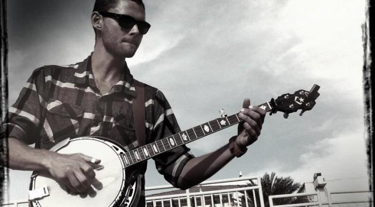 Man playing banjo outside.