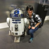 Digital Arts student poses in front of replica of Star Wars character R2D2