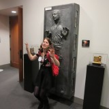 Digital Arts student poses in front of replica of frozen Han Solo