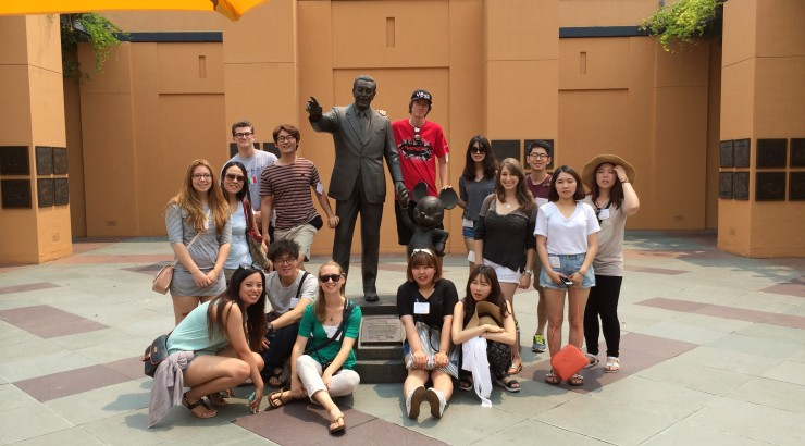 Image of Chapman Students posing with the Walt Disney statue outside of Disney Studios