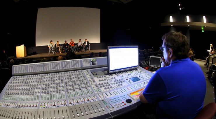 man sitting at sound board during presentation