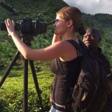 student framing camera in tropical landscape