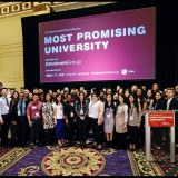 large group standing in front of a screen that says most promising university