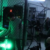 green lit storage room with man inside and cameras pointed at him