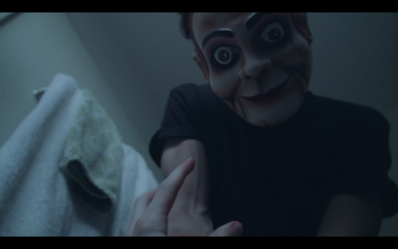 ventriloquist's dummy looking at a person in bed