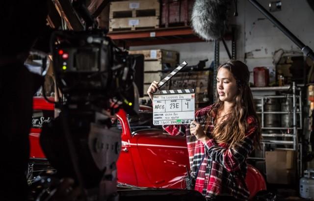 woman on a film setting holding a slate