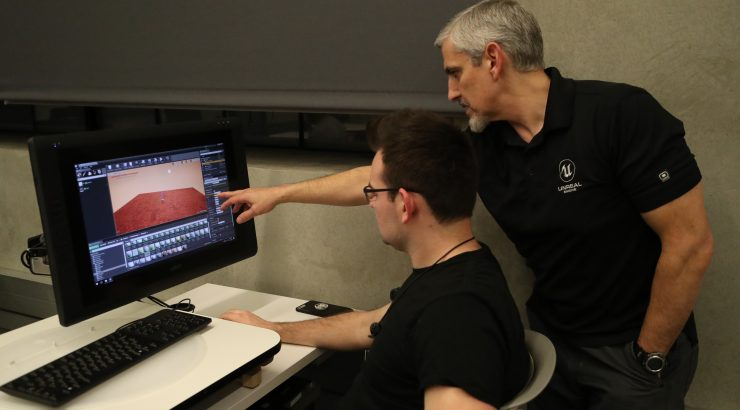 Professor and student at a computer in a virtual reality workshop