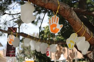 Photograph of painted hands hanging from a tree branch