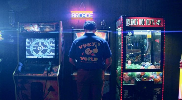 Man playing arcade game, seen from behind
