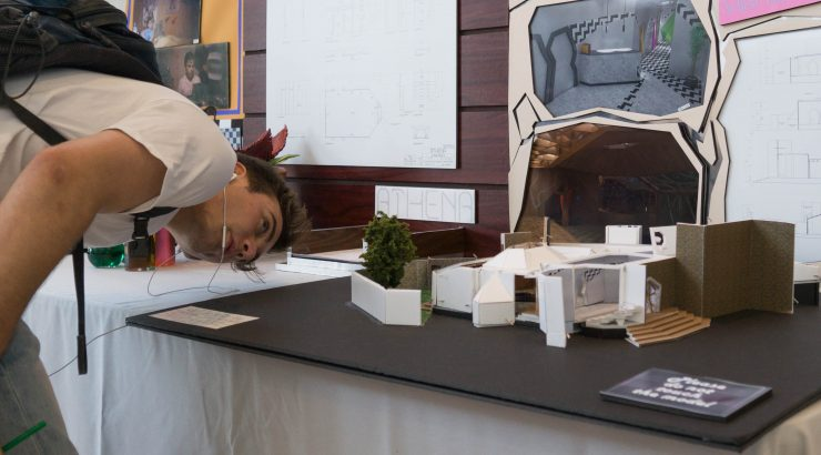 A visitor looks closely at the details of a miniature for the Production Design Showcase