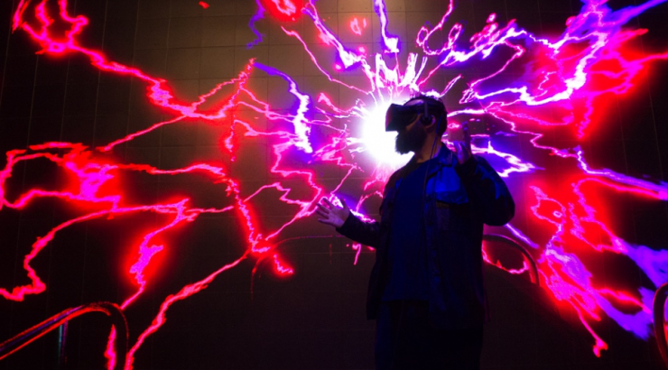 Jon Schnitzer pictured in a VR experience of neon pink electricity waves