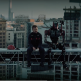 man and robot sit on skyscraper