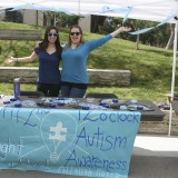 Two women pose in support of autism awareness.