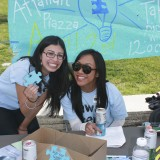 Two women pose with a puzzle piece in support of autism awareness.