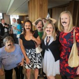 From Left to Right: Maria Lynch, Breann Parker, Kathy Arballo, Laura Burns, and Anna Lane showing their support for Dr. Mike Madrid by wearing his trademark mustache.