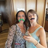 Two women posing with fake mustaches.