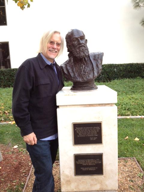 Dr. Peter McLaren standing next to the Paulo Freire bust at Chapman University