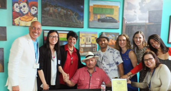 victor villasenor at ces santa ana bookstore attallah college of  group of people smiling in front of works of art victor villasenor