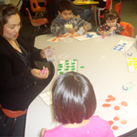 Woman sits at table with children, playing a game.