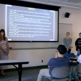 Four people in front of a screen present to a group.