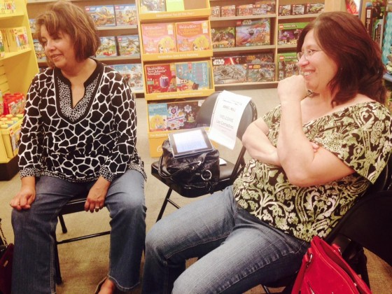 Two women sit in a toy store.