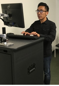 Man stands at a computer, typing.
